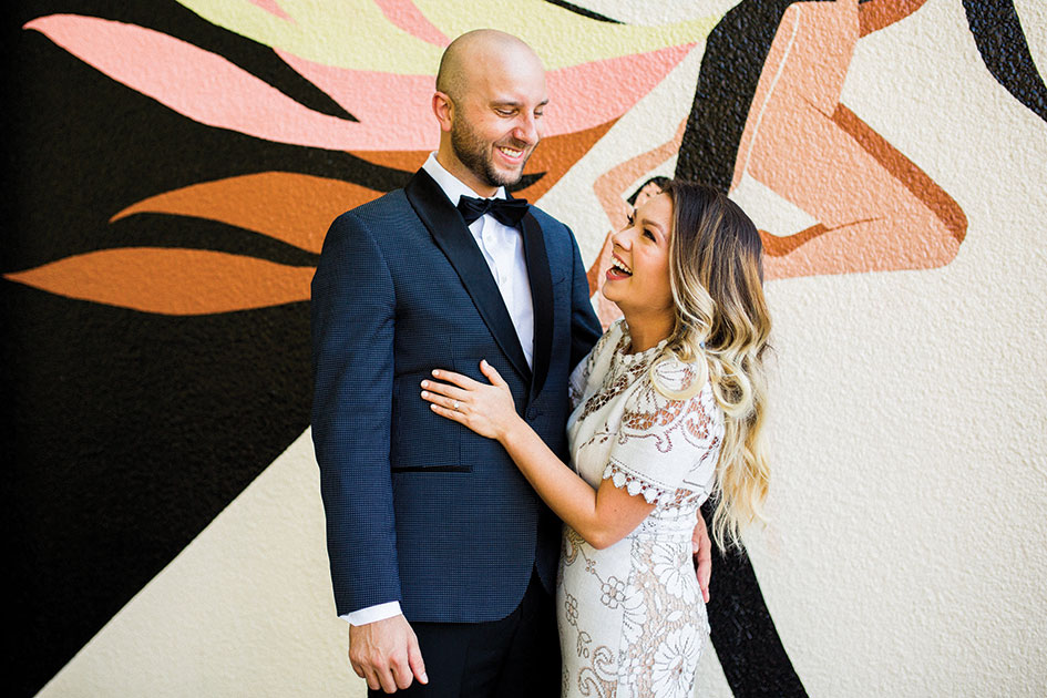 The couple stands together in front of a dusty pink and orange mural at Coopers Hall