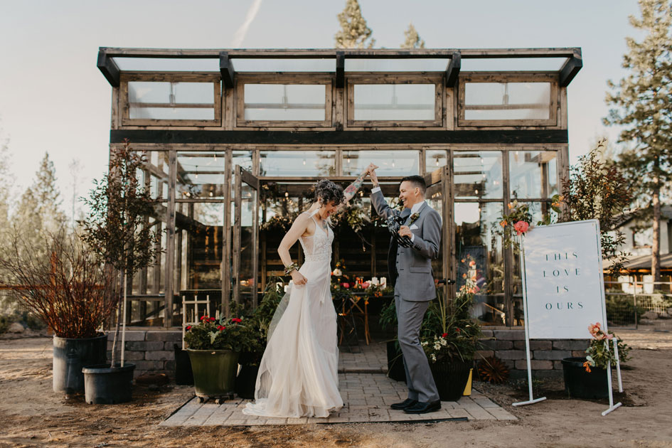 The couple stands outside a greenhouse overflowing with local blooms.
