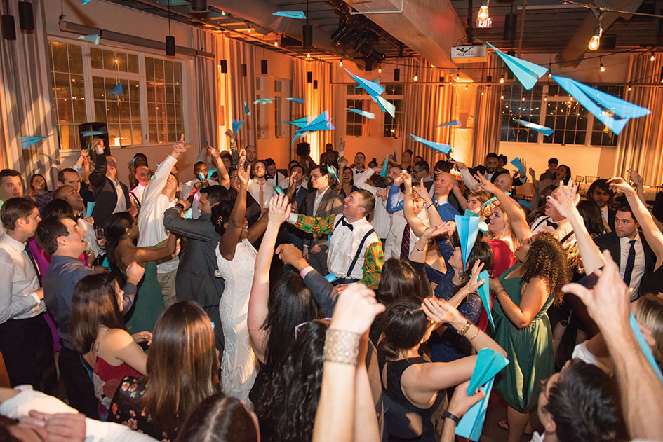 A paper-airplane toss at this travel-themed wedding lent a fun moment to the dance party.