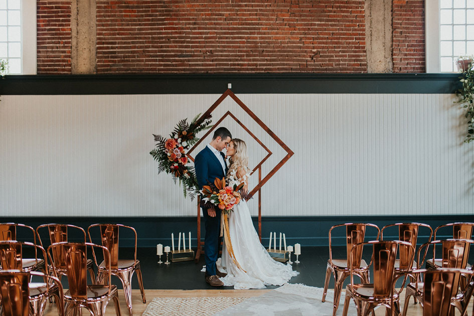 A geometric arch with tropical florals as a ceremony backdrop at The Evergreen in Portland