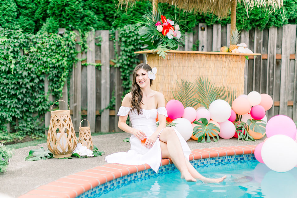 The bride relaxes in the pool near a balloon installation with a drink in hand.