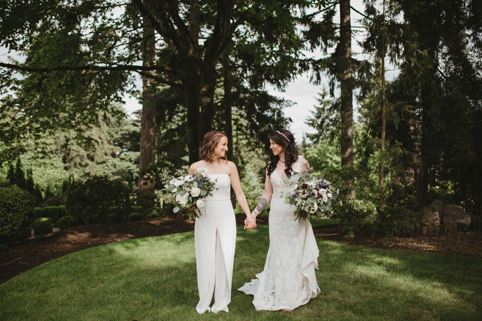 Erika and Stacey standing under a grove of pines at a private estate.