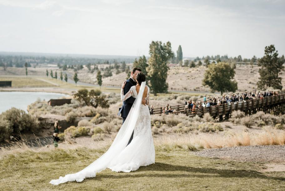 The hills and valleys of Central Oregon span beyond the couple as they pose at Brasada Ranch