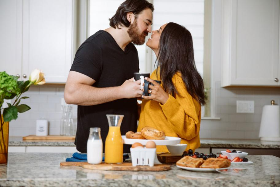 Bride and groom stand in their kitchen at breakfast for their engagement photography session.