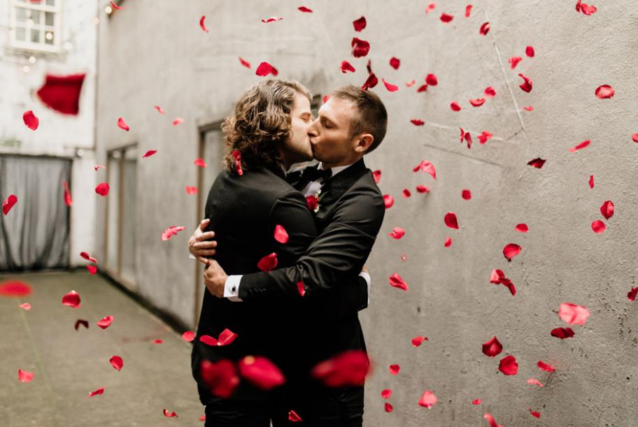 The grooms in a shower of rose petals at The West End Ballroom in Oregon.