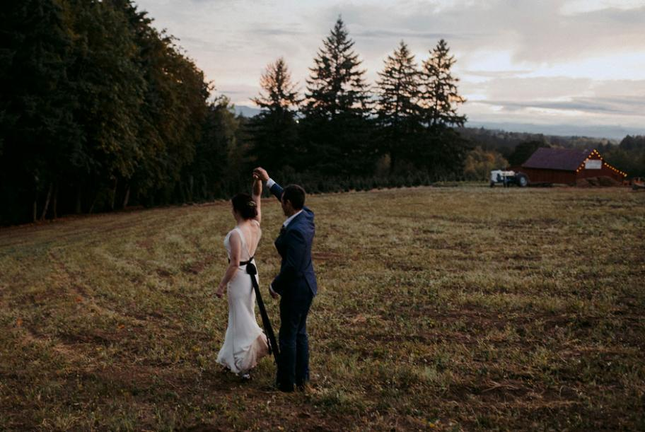The bride and groom dance in a field at sunset.